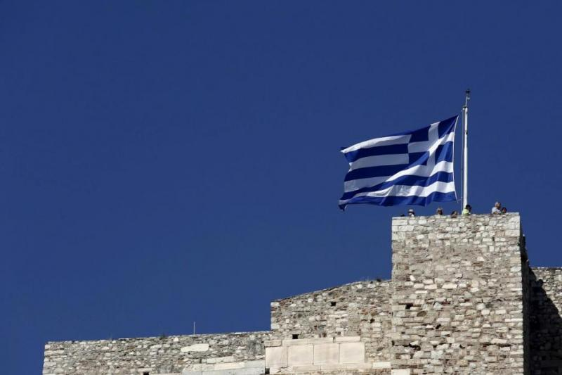 Tourists stand under a Greek national flag atop the Acropolis hill in Athens, June 14, 2015. REUTERS
