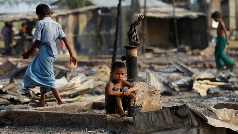 A boy sits amid the wreckage of shelters destroyed by a fire at a camp for displaced Rohingya near Sittwe, the Rakhine capital, in May 2016. REUTERS/Soe Zeya Tun