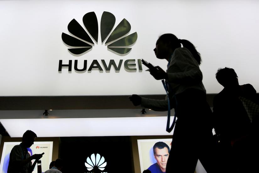 People walk past a sign board of Huawei at CES (Consumer Electronics Show) Asia 2016 in Shanghai, China May 12, 2016. REUTERS FILE PHOTO