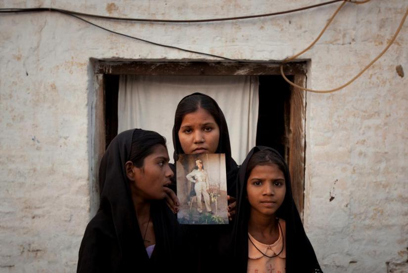 The daughters of Pakistani Christian woman Asia Bibi pose with an image of their mother while standing outside their residence in Sheikhupura located in Pakistan`s Punjab Province November 13, 2010. Standing left to right is Esha, 12, Sidra, 18 and Eshum, 10. REUTERS/FILE PHOTO