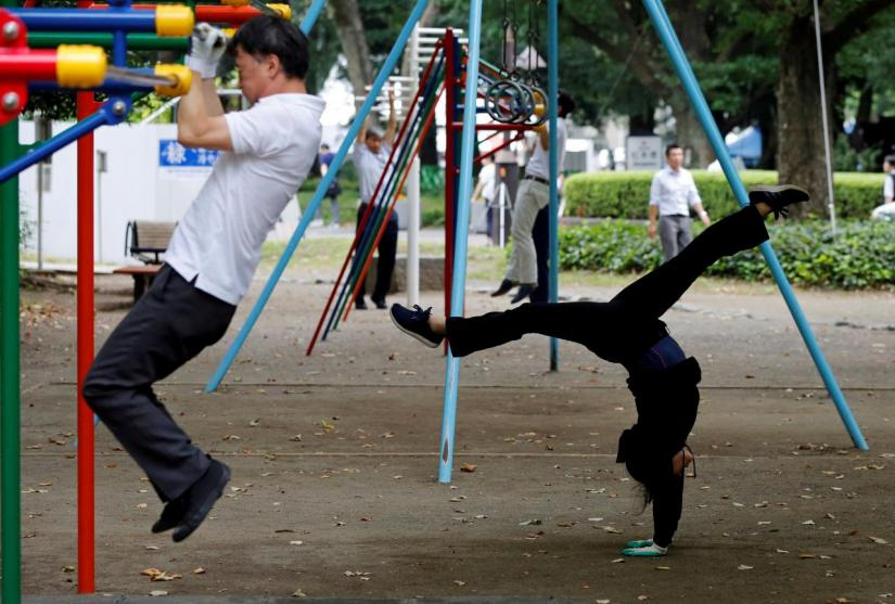 Office workers exercise during their lunch break at a park in central Tokyo, Japan September 22, 2017. REUTERS/FILE PHOTO