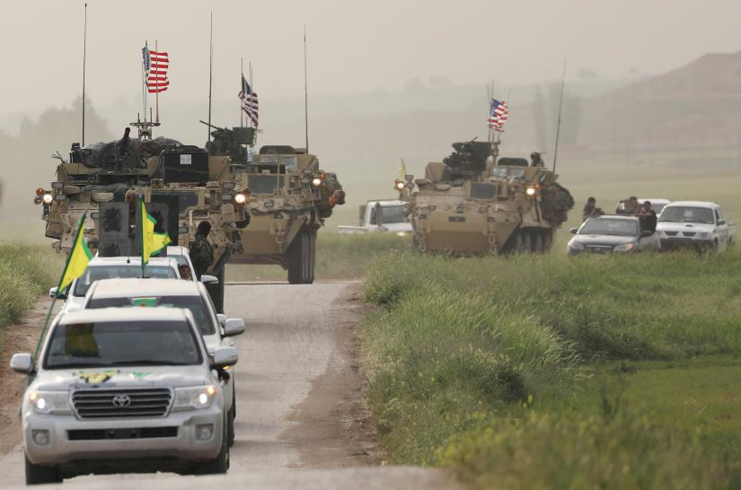 Kurdish fighters from the People`s Protection Units (YPG) head a convoy of U.S military vehicles in the town of Darbasiya next to the Turkish border, Syria April 28, 2017. REUTERS/file photo