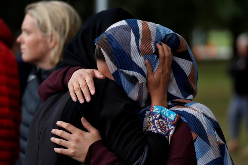 Women embrace near Masjid Al Noor mosque in Christchurch, New Zealand, March 17, 2019. REUTERS