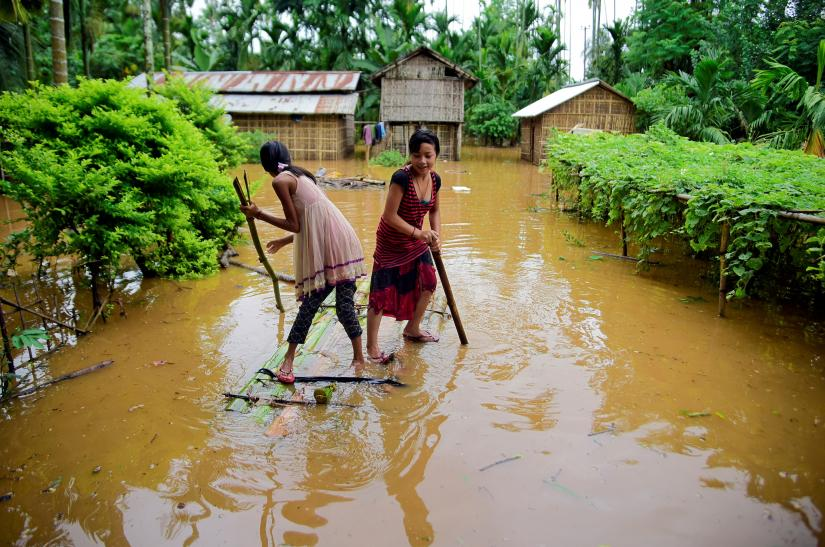 Girls row a makeshift raft past submerged houses at a flood-affected village in Karbi Anglong district, in the northeastern state of Assam, India, July 11, 2019. REUTERS/File Photo