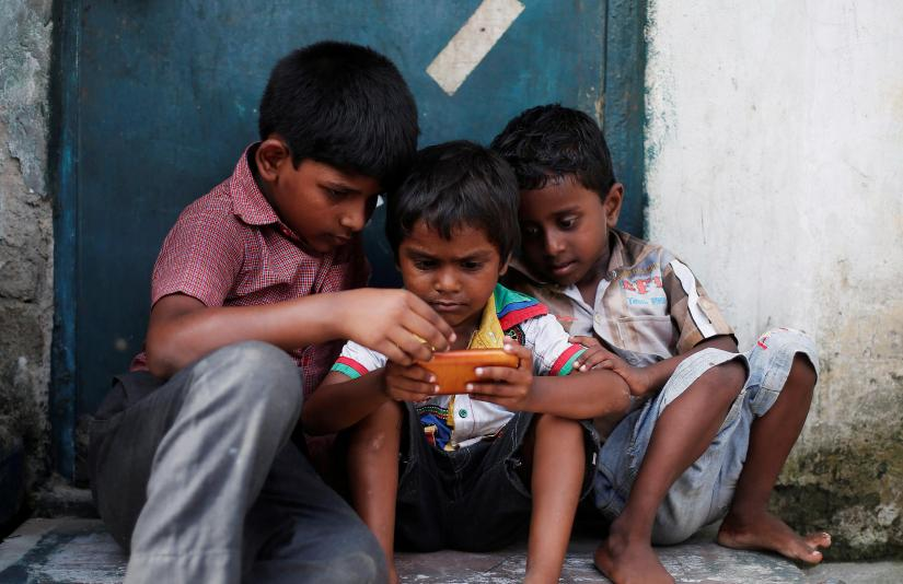 Children play a game on a mobile phone at slum area in New Delhi, India July 4, 2017. REUTERS