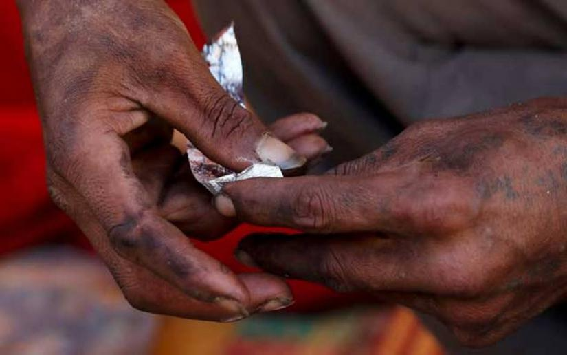 A homeless drug user demonstrates using an empty piece of foil how he usually prepares drugs for use at his tent in Loikan, Shan State, Myanmar January 25, 2019. Picture taken January 25, 2019. REUTERS/Stringer