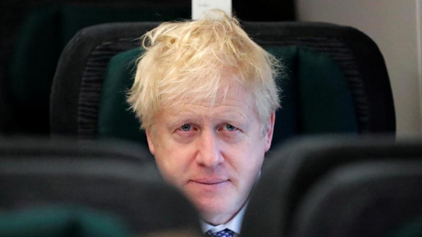 FILE PHOTO: Britain`s Prime Minister Boris Johnson looks up as he sits on a train, on his way to an election campaign event near Castle Cary, Britain Nov 14, 2019. Frank Augstein/Pool via REUTERS