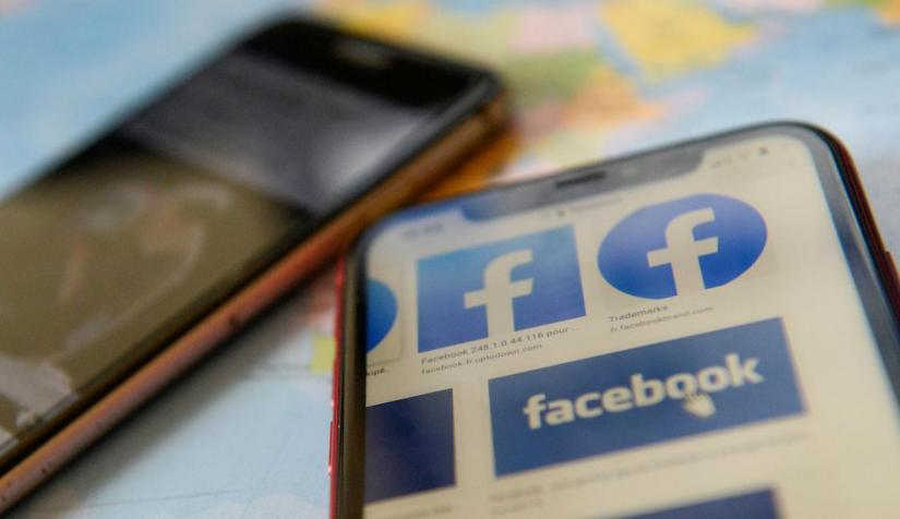 FILE PHOTO: Facebook logos are seen on a mobile phone in this picture illustration taken Dec 2, 2019. REUTERS
