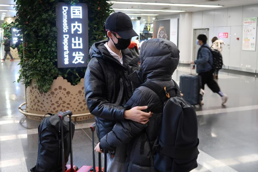 Passengers wearing masks are seen at the terminal hall of the Beijing Capital International Airport, in Beijing