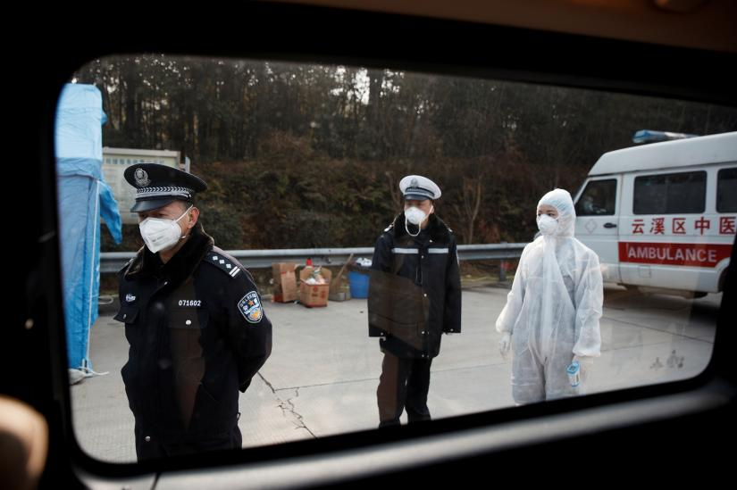 A medical worker in protective suit and police officers wait for drivers at a checkpoint in Yunxi county, Hunan province, near the border to Hubei province, on virtual lockdown after an outbreak of a new coronavirus, in China, January 28, 2020. REUTERS