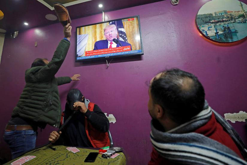 A Palestinian man hits with a shoe a television screen broadcasting the announcement of Mideast peace plan by U.S. President Donald Trump, in a coffee shop in Hebron in the Israeli-occupied West Bank January 28, 2020. REUTERS