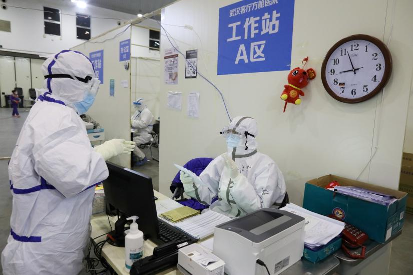 Medical workers in protective suits are seen inside the Wuhan Parlor Convention Center that has been converted into a makeshift hospital following an outbreak of the novel coronavirus, in Wuhan, Hubei province, China February 15, 2020. Picture taken February 15, 2020. China Daily via REUTERS