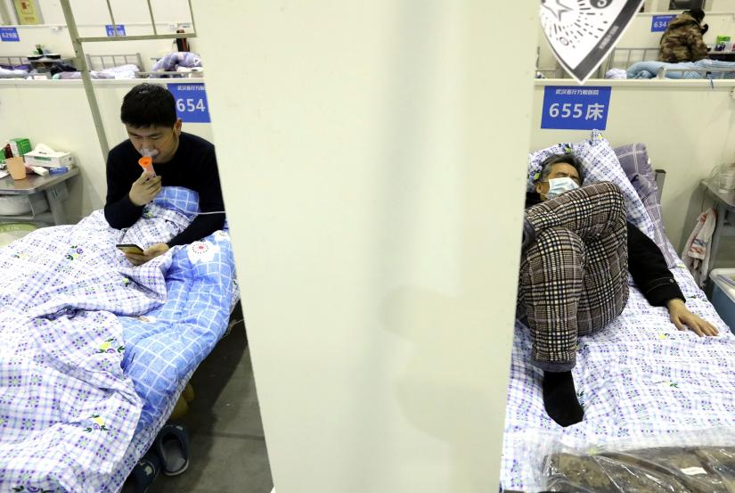 Patients rest on their beds inside the Wuhan Parlor Convention Center that has been converted into a makeshift hospital following an outbreak of the novel coronavirus, in Wuhan, Hubei province, China February 15, 2020. Picture taken February 15, 2020. China Daily via REUTERS