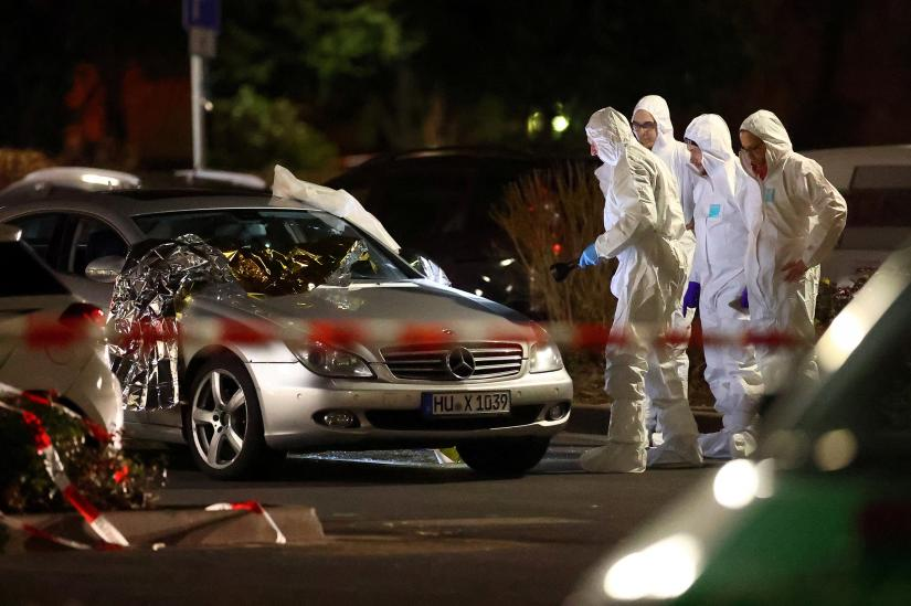 Forensic experts work around a damaged car after a shooting in Hanau near Frankfurt, Germany, February 20, 2020. REUTERS