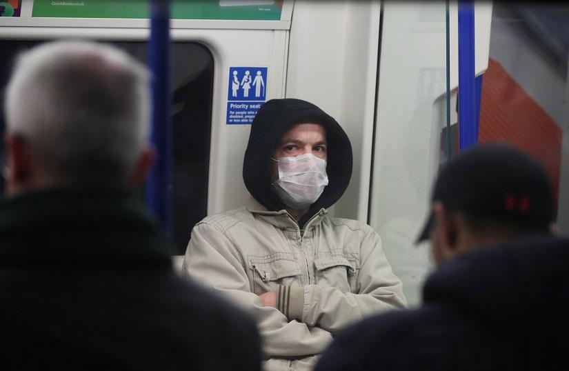 FILE PHOTO: A commuter wearing a protective face mask on a train at Clapham North underground station as the number of coronavirus (COVID-19) cases grow around the world, in London, Britain, Mar 18, 2020. REUTERS