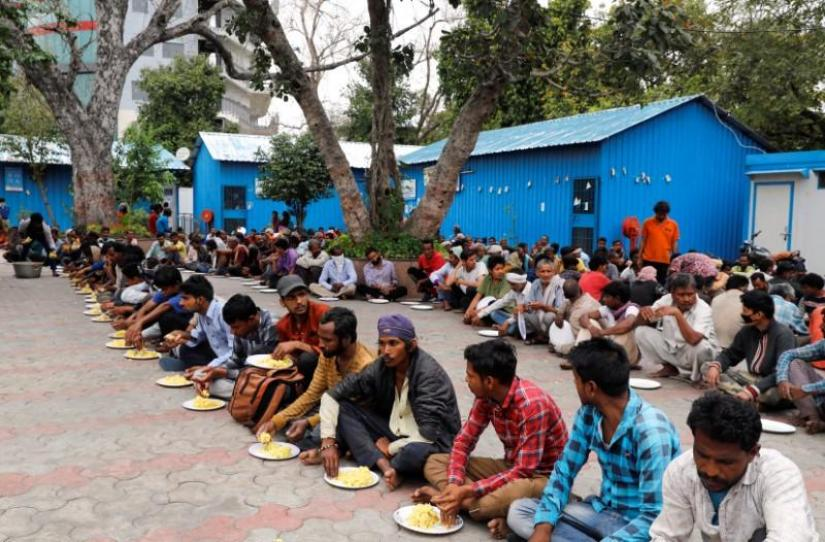 Daily wage workers and homeless people eat food inside a government-run night shelter during a 21-day nationwide lockdown to limit the spreading of coronavirus disease (COVID-19), in the old quarters of Delhi, India, Mar 26, 2020. REUTERS