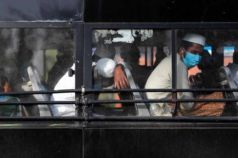 Men wearing protective masks sit inside a bus that will take them to a quarantine facility, amid concerns about the spread of coronavirus disease (COVID-19), in Nizamuddin area of New Delhi, India, Mar 31, 2020. REUTERS